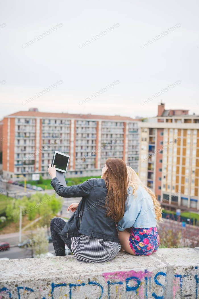 zwei junge blonde und Brünette Mädchen chatten und mit technolog