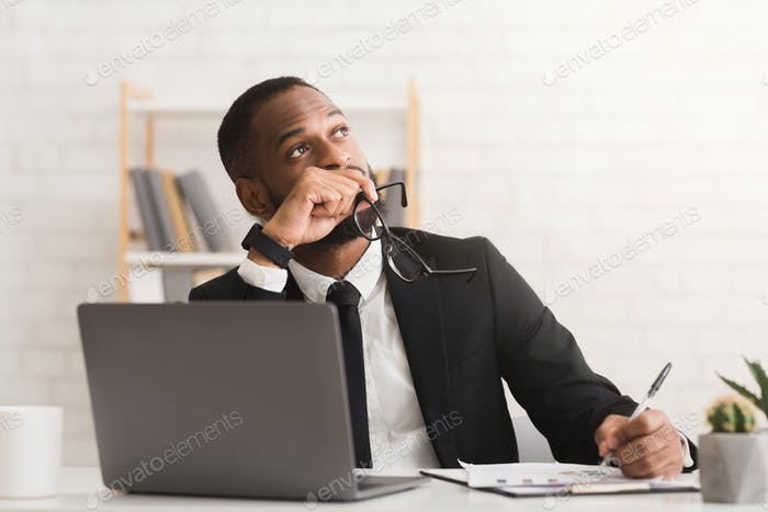 Pensive young businessman working on new business plan in office