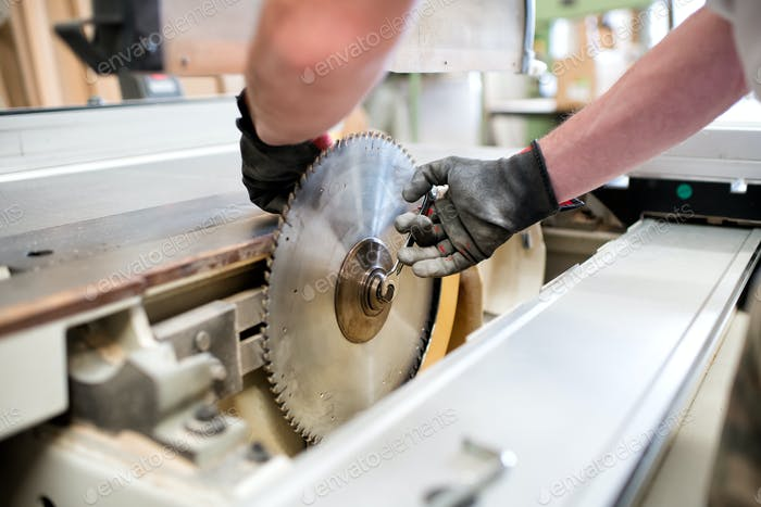 Carpenter in a workshop changing a saw blade