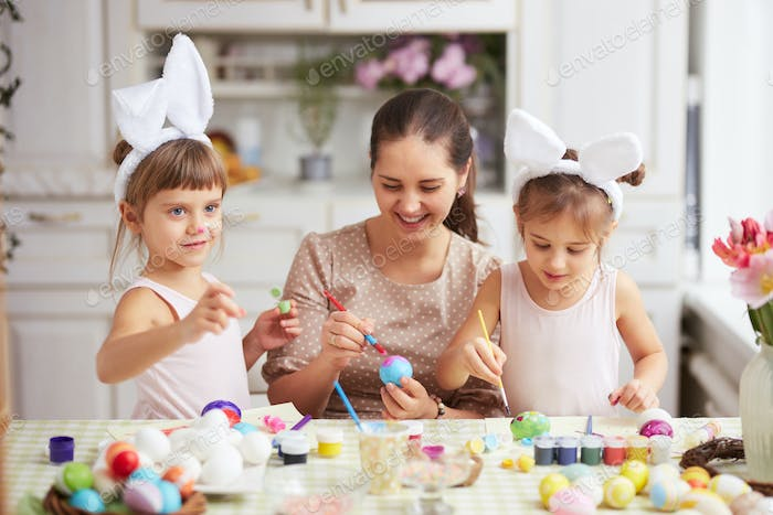 Happy young mother and her two little daughters with white rabbit's ears on their heads dye the