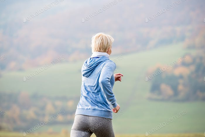 Young woman running in autumn nature, rear view