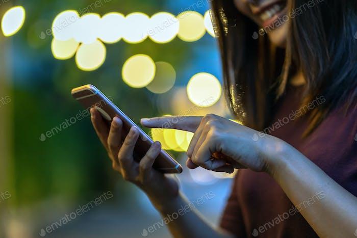 Primer plano de la mano de la mujer asiática usando el teléfono inteligente y la pantalla táctil en el parque al aire libre
