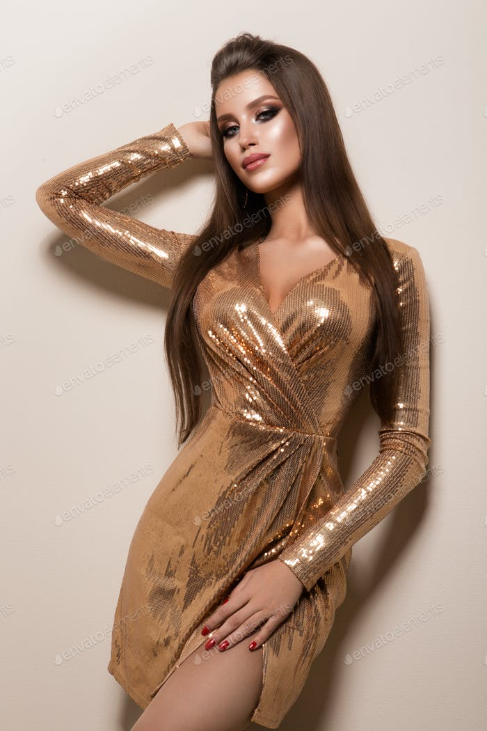 Beautiful woman with professional make up. Gold dress