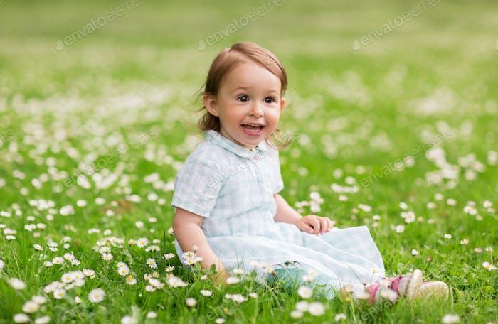 glückliches Baby Mädchen auf grünem Sommerfeld