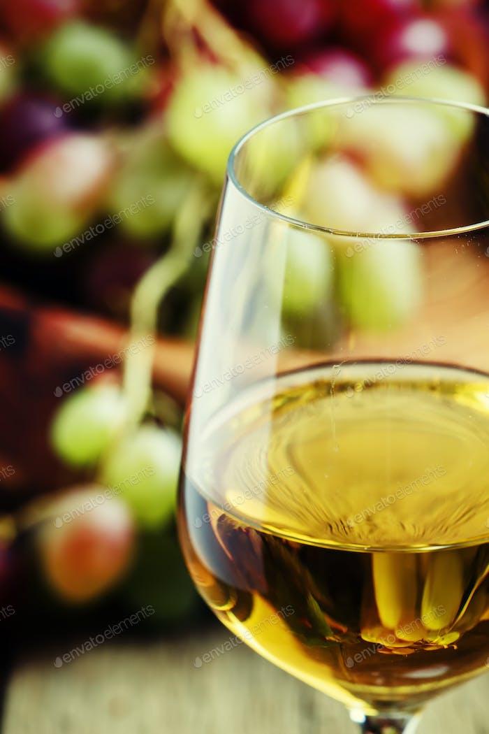 Weißwein in einem Glas mit Herbsttrauben