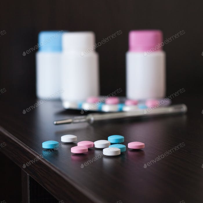 Pills And Thermometer On Brown Table