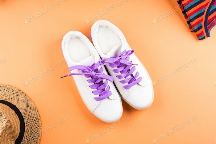 Fashion flat lay with white sneakers on orange