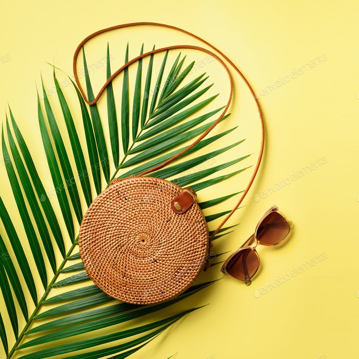 Round rattan bag, sunglasses on yellow background. Square crop. Top view with copy space. Trendy