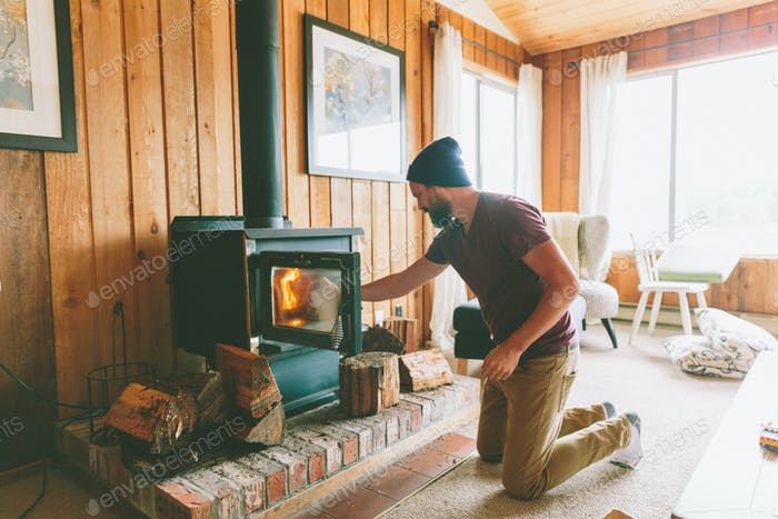Man Making a Fire at a Cabin