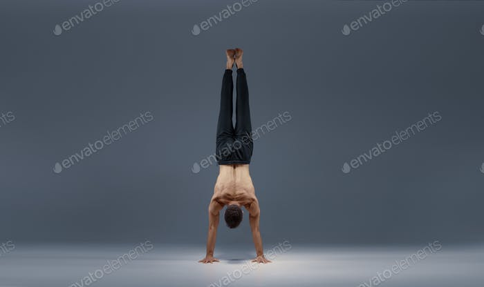 Male yoga does split on hands, back view