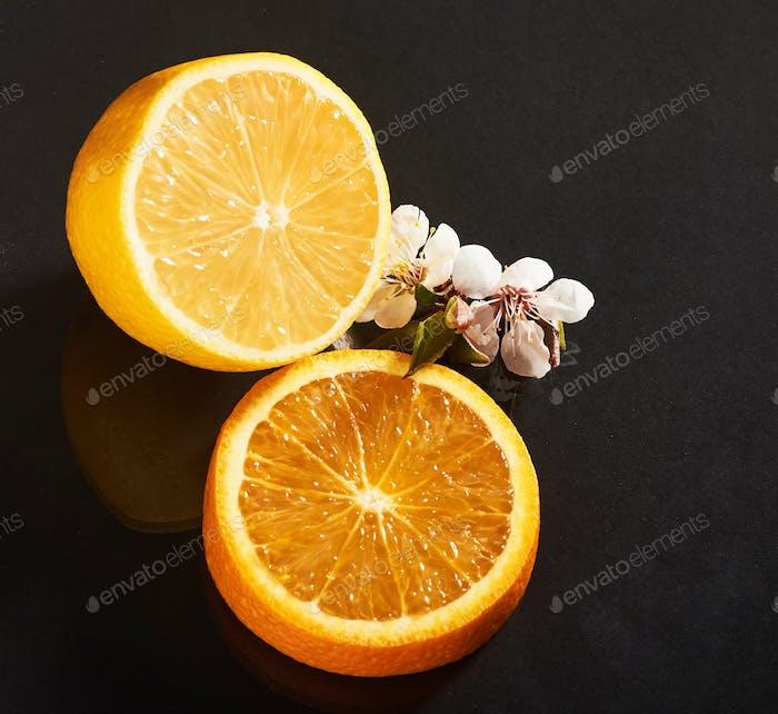 Köstliche und saftige Orange und Zitrone isoliert auf schwarzem Hintergrund.