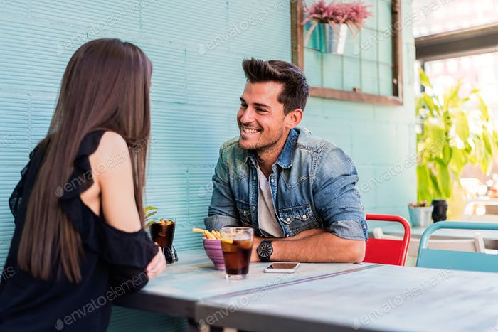 Happy young couple seating in a restaurant