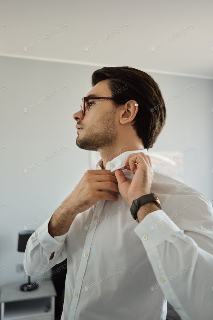 Young attractive man in white shirt and eyeglasses thoughtfully looking aside at modern home