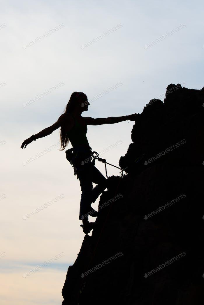 Beautiful girl physique climbing a rocky wall