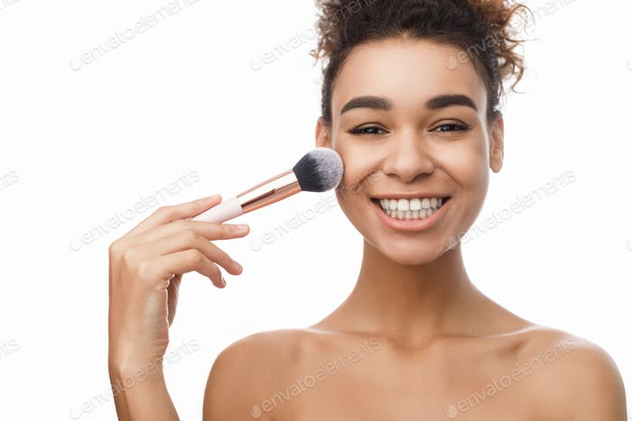 Smiling woman applying powder on face with brush tool