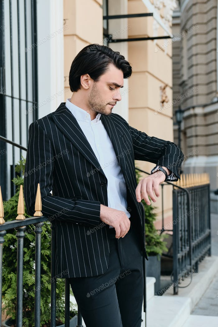 Young brunette man in classic striped jacket dreamily looking on watch standing on city street