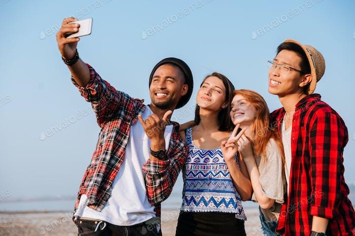 Fröhliche Menschen stehen und machen selfie mit Handy im freien
