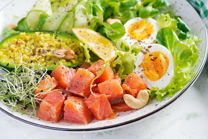 Ketogenic diet breakfast. Salt salmon salad with greens, cucumbers, eggs and avocado.