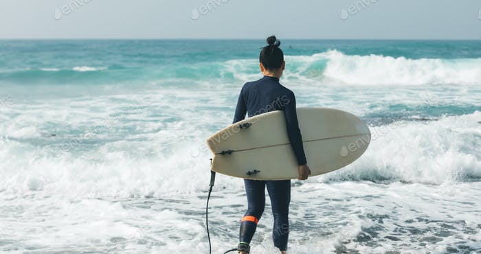 Surfer with surfboard going to surf