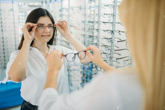 Female optician and buyer chooses glasses frame