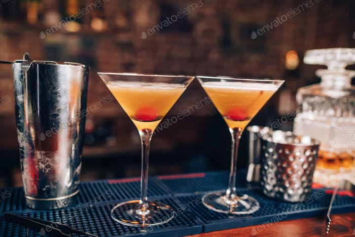 Two fresh alcoholic cocktails on bar counter. Close up of bar details with beverages and drinks