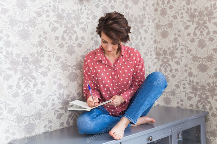 Girl sitting on chest of drawers at home