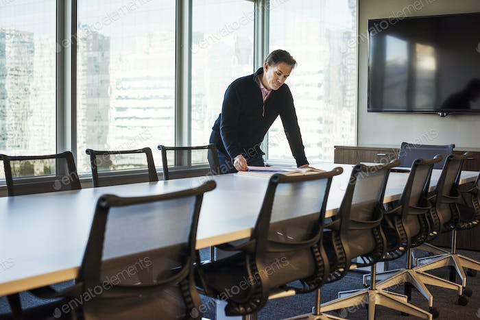 A man standing at a table in a meeting room looking down at an open book.