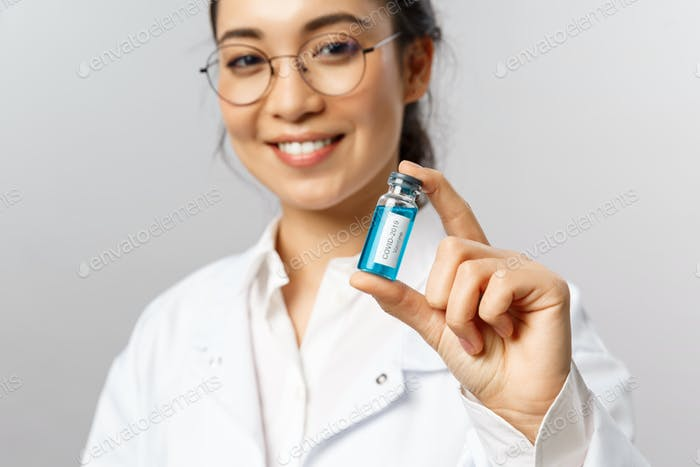 Close-up portrait of young professional asian doctor, researcher or infectionist, giving patient