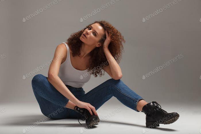 casual clothing mixed race curly woman on gray background