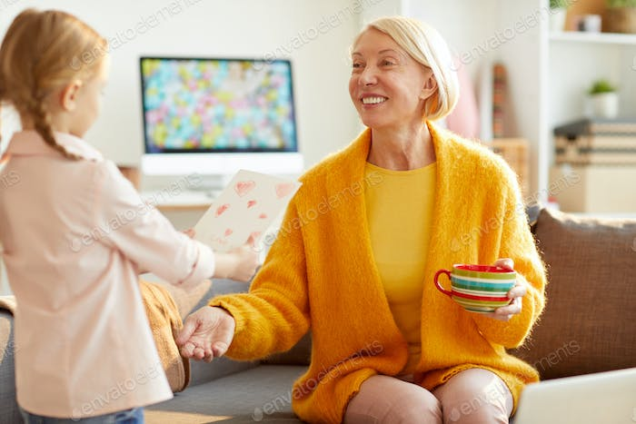 Cute Girl Giving Card to Mom