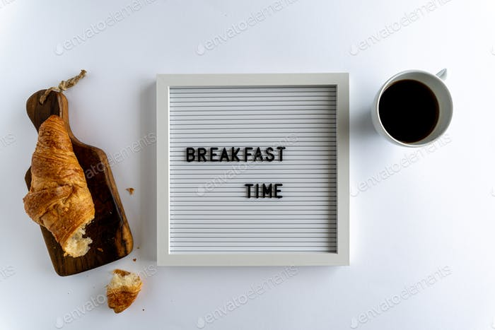 Letterboard With Words That Spell Breakfast Time, with a crumbly croissant and a cup of coffee