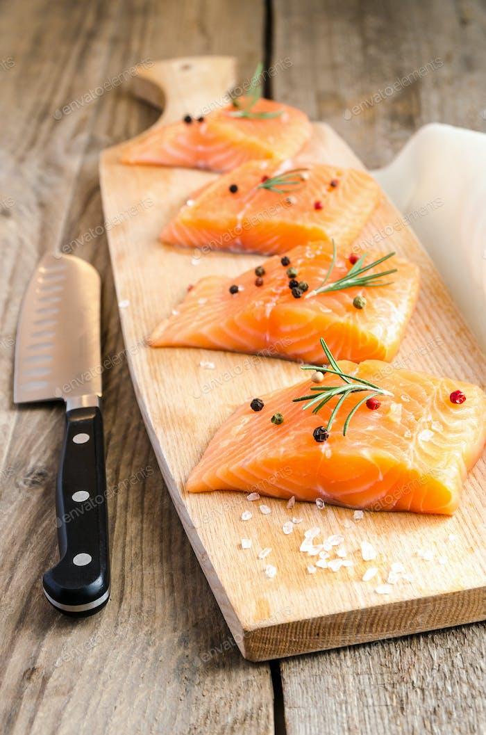 Raw salmon steaks on the wooden board
