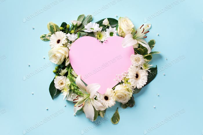 Creative layout with white roses, lily, gerbera, pink paper heart over blue background. Top view