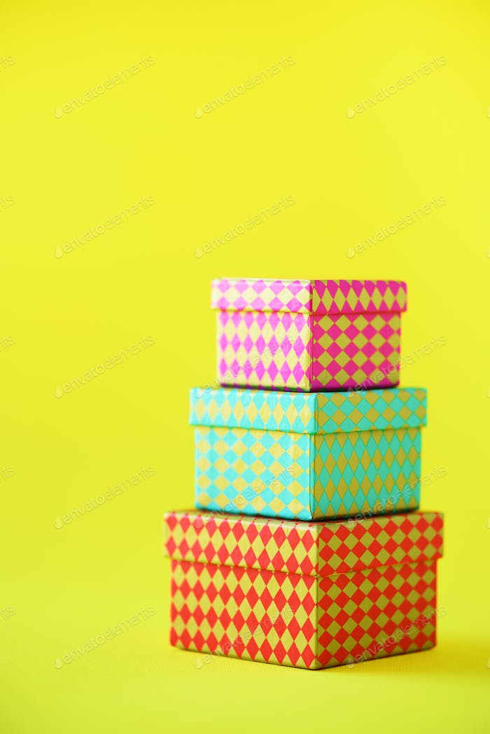 Collection of colorful gift boxes on yellow background. Presents for birthday and party. Christmas