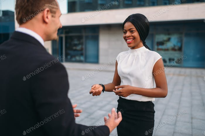 Business woman and businessman, outdoors meeting