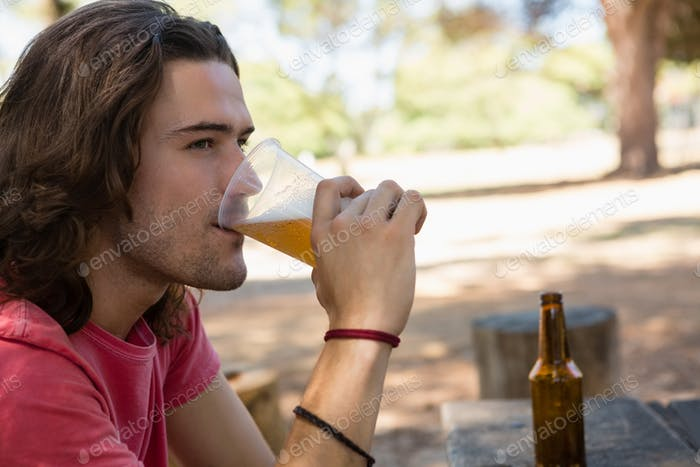 Man drinking beer from disposable glass