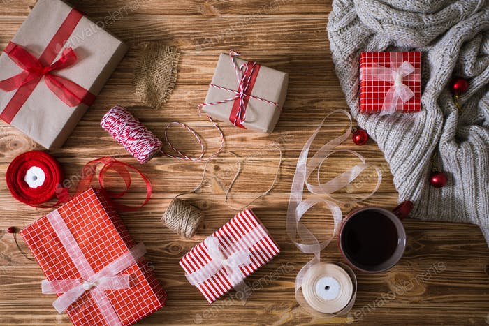 Christmas gifts in paper and tied with red and white threads and a cup of tea on wooden background