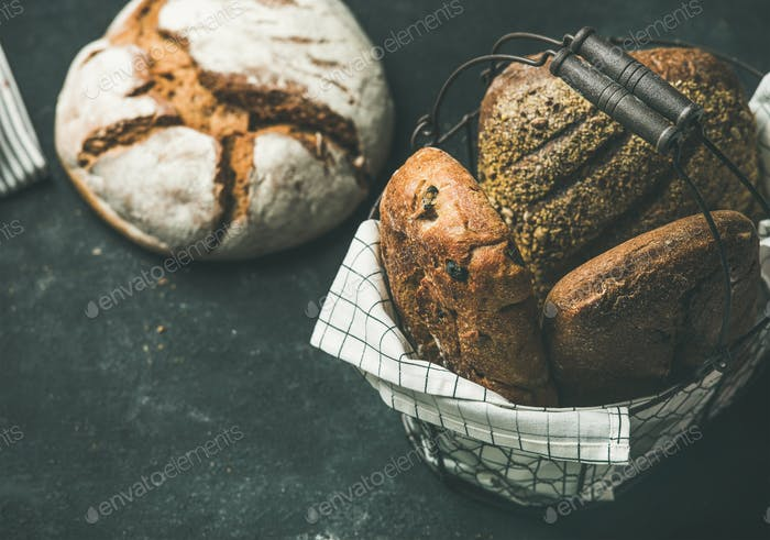 Various bread loaves over black background, copy space