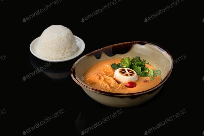 Spicy Thai soup Tom Yam on dark background