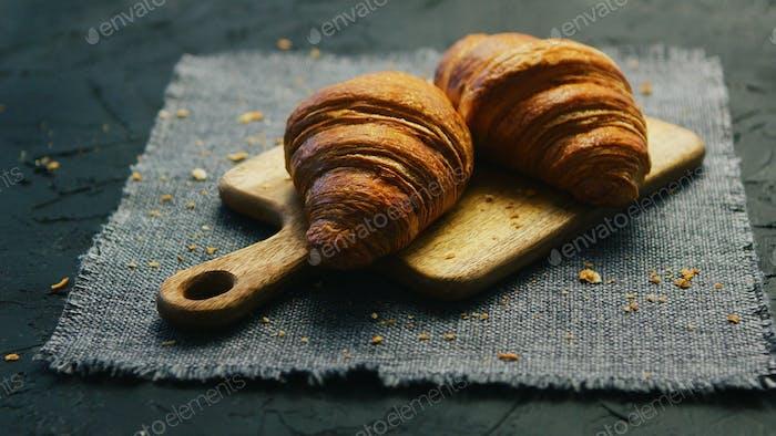 Fresh croissants on chopping board