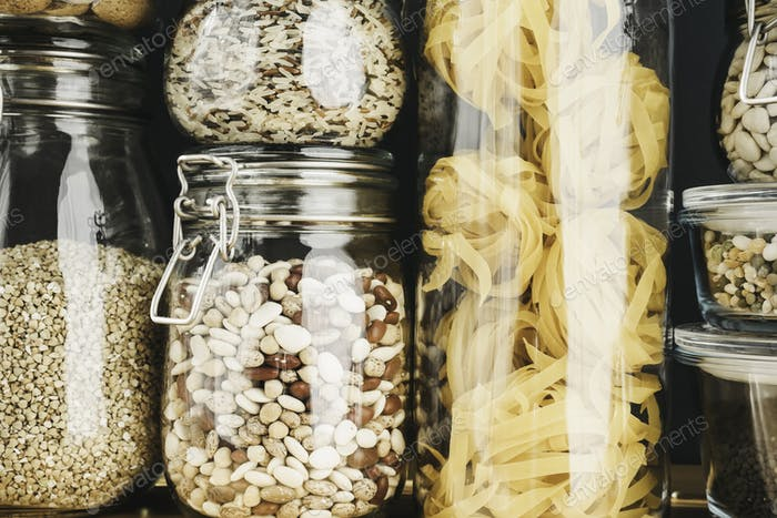 Assortment of grain products and pasta in glass storage containers on wooden table. Healthy cooking