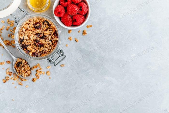 Gesundes Frühstück Müsli mit frischer Himbeere und Honig auf grauem Stein Hintergrund