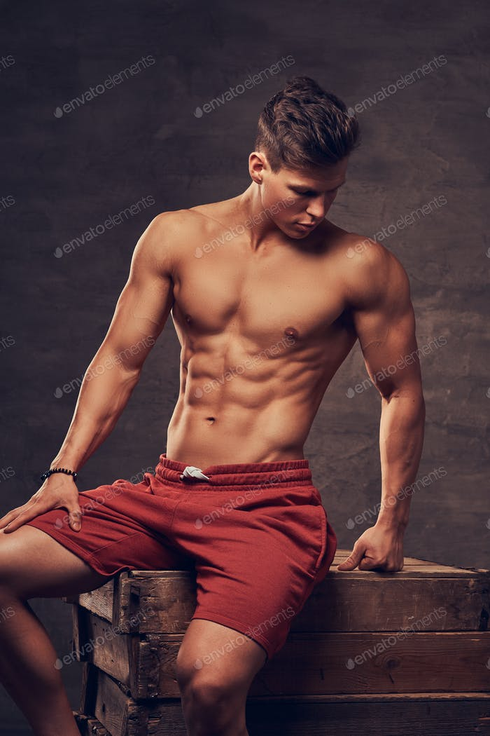 Sexy shirtless young man model in red shorts posing at a studio while sitting on wooden boxes.