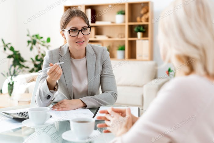 Confident young auditor with pen sitting in front of client and consulting her