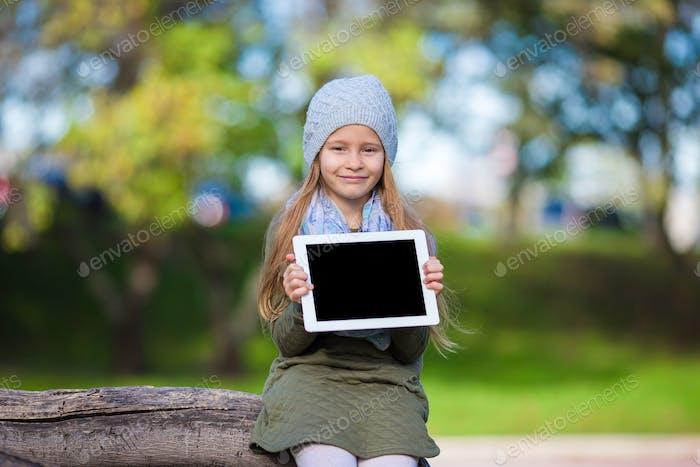 Entzückende kleine Mädchen halten Tablet-PC im Freien im Herbst sonnigen Tag