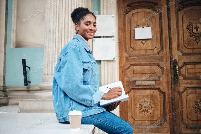 Beautiful African American student girl in denim jacket with notebook studying outdoor