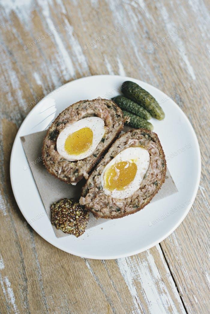 Eine Mahlzeit auf einem Teller, ein Scotch Ei halbieren mit Beilagen.