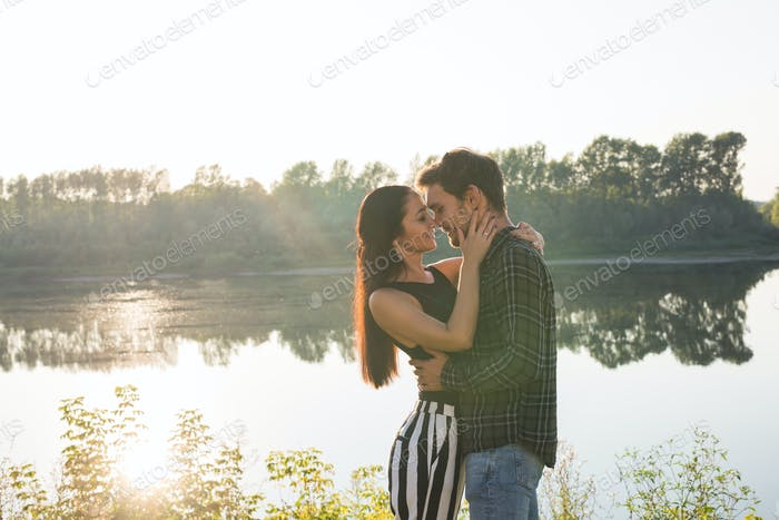 People, love and nature concept - Portrait of young beautiful couple embracing each other over water