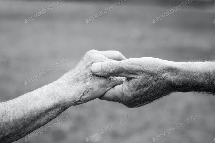 Close-up of elderly couple holding hands