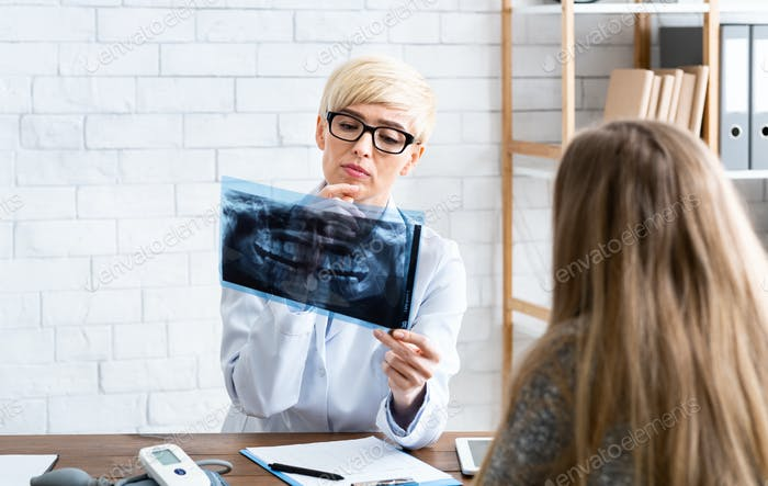 Woman dentist examines x-ray of patient in interior of office